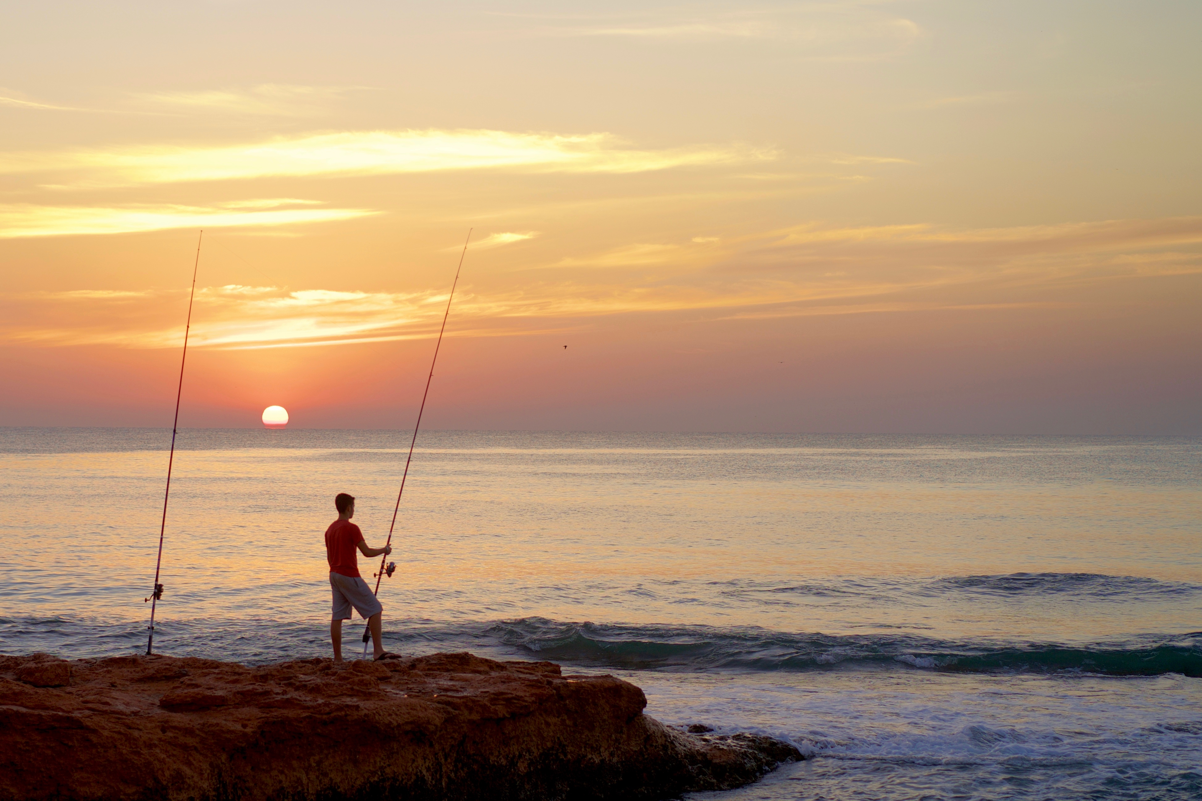 The fisherman and his rods are the focus of this sunrise shot.